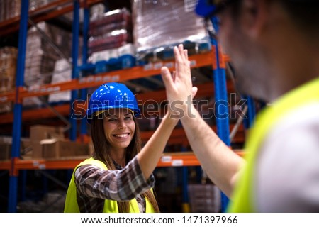 Warehouse workers giving high five to each other. Industrial workers hands touching and clapping for successful job done. Positive atmosphere at job. Teamwork concept. Royalty-Free Stock Photo #1471397966