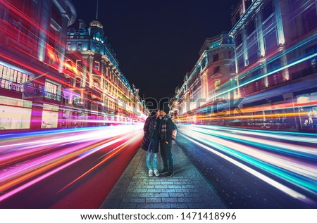 Kissing couple in the center of Regent Street, London at night #1471418996