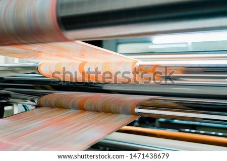Rotogravure Printing method. It is one of flexible packaging process. Plan film was printed each color thru cylinder. Machine is running in high speed mode. This system is suitable for repeated work. Royalty-Free Stock Photo #1471438679