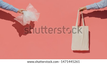 Reusable shopping bag instead of thousands of plastic bags. Eco trend to reduce disposable plastic. Hands on pink background holding plastic bags and cotton shopper bag. #1471445261
