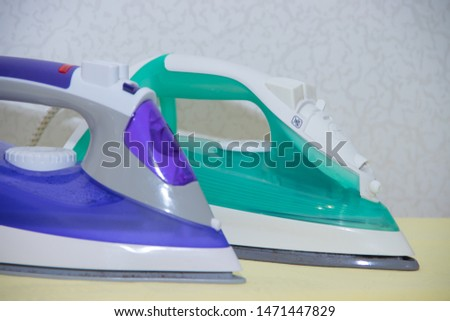 Two irons on an ironing board. Selection and comparison of irons. Ironing board. #1471447829