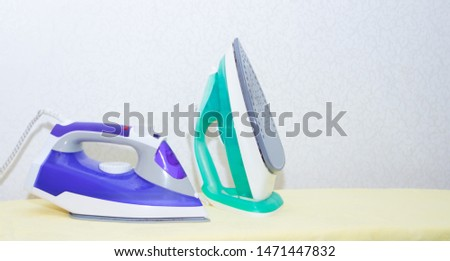Two irons on an ironing board. Selection and comparison of irons. Ironing board. #1471447832