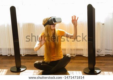 Young woman wearing virtual reality goggles vr box with arms outstretched sitting on floor in living room, listening to music. Connection, technology, new generation and progress concept. #1471471814