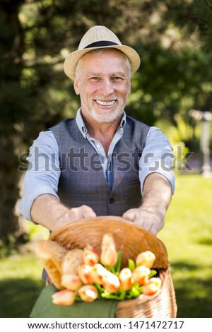 Happy man holding a basket with flowers #1471472717