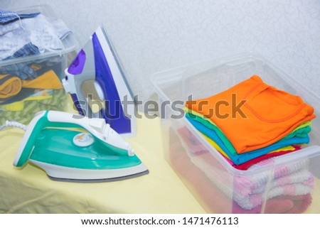 Iron and baby clothes. Colored clothes on an ironing board. Bright t-shirts. Ironed and non-ironed colored children's underwear on the board. Ironing board. A pile of things. #1471476113