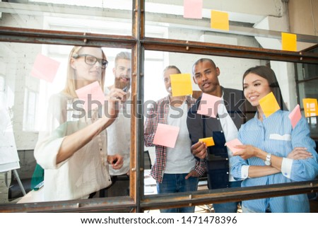 Sharing business ideas. Young modern people in smart casual wear using adhesive notes while standing behind the glass wall in the board room #1471478396
