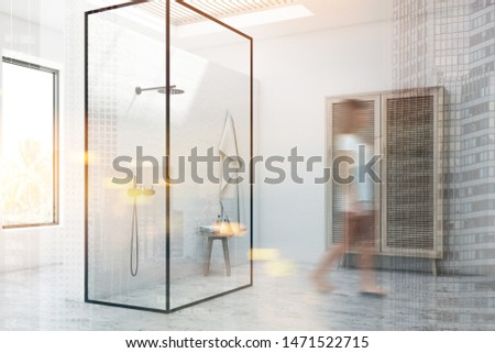 Young woman walking in modern bathroom corner with white walls, shower stall with glass walls and comfortable wardrobe. Toned image double exposure blurred #1471522715