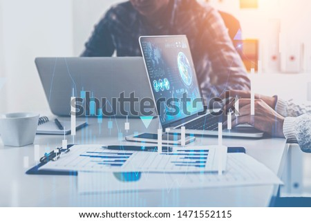 Business people working with laptops in blurred office with double exposure of business infographics and graphs. Market analysis concept. Toned image. Elements of this image furnished by NASA #1471552115