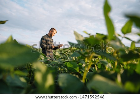 Portrait of young farmer standing in soybean field. #1471592546