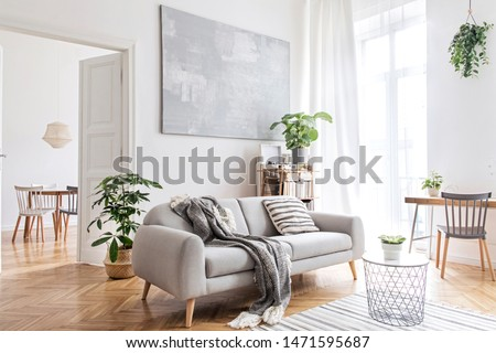 Stylish scandinavian living room with design furniture, plants, bamboo bookstand and wooden desk. Brown wooden parquet. Abstract painting on the white wall. Nice apartment. Modern decor of bright room #1471595687