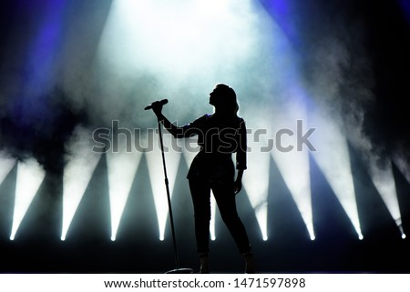 Vocalist singing to microphone. Singer in silhouette. Royalty-Free Stock Photo #1471597898