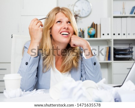 Frustrated tired businesswoman sitting at workplace among crumpled papers #1471635578
