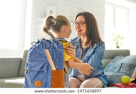 Parent and pupil of preschool. Woman and girl with backpack behind back. Beginning of lessons. First day of fall. #1471658897