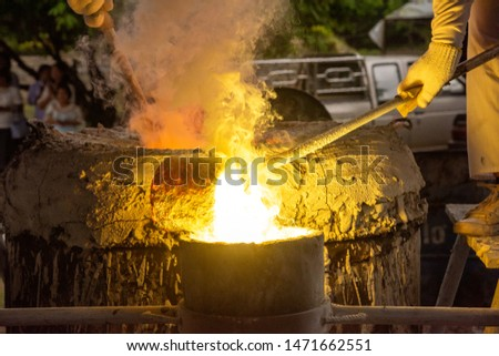 Melting metal is poured into the mold. Step of casting Buddha images.  W #1471662551