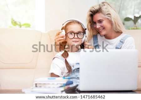 A child sits at a computer with a young beautiful girl as a teacher and learns remotely. The concept of home schooling. Online training. #1471685462