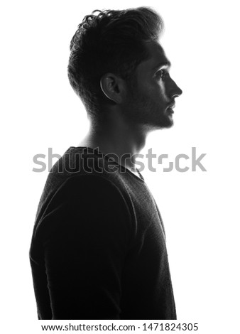 Young attractive European male model silhouette with modern hair style posing on white isolate background.