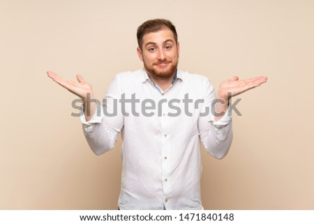 Blonde man over isolated background having doubts while raising hands #1471840148