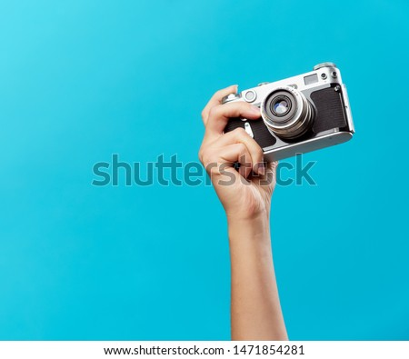 Image of hand with phone on empty blue background Royalty-Free Stock Photo #1471854281