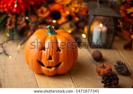Halloween pumpkin with leaves on an old wooden table with luminous lights and an old lamp. Autumn mood and atmospheric photo #1471877345