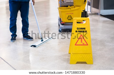 """Janitor Cleaning Floor In Front Of Yellow Caution """"Cleaning in progress"""". Cleaning service in public area. #1471880330"""