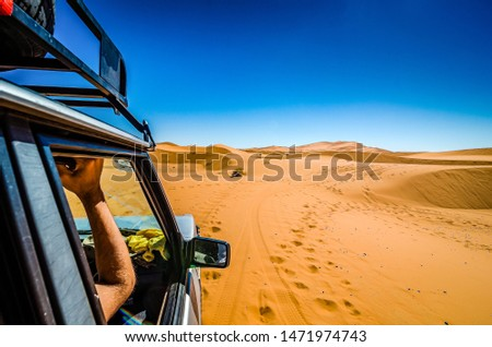 Off road car learning how to drive in sand dunes in Erg Chebbi, Morocco Royalty-Free Stock Photo #1471974743