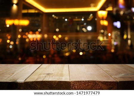 background Image of wooden table in front of abstract blurred restaurant lights #1471977479