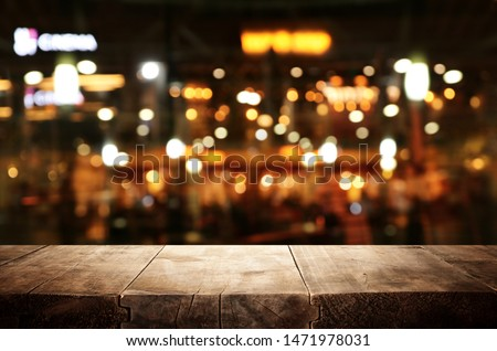 background Image of wooden table in front of abstract blurred restaurant lights #1471978031