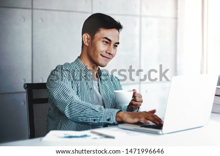 Happy Young Businessman Working on Computer Laptop while Drinking Coffee in Office #1471996646