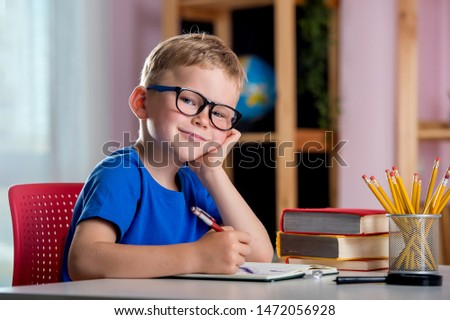 Back to school. Thinking child boy writing, drawing in notebook sitting at desk and doing homework. Pupil of primary school in class writing and reading. Home schooling and education at home Royalty-Free Stock Photo #1472056928