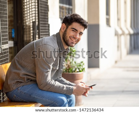 Fashion college man in his twenties happy checking blog or chatting on the internet with friends on smart mobile phone app in european outdoors city. In communication technology and travel Europe. #1472136434