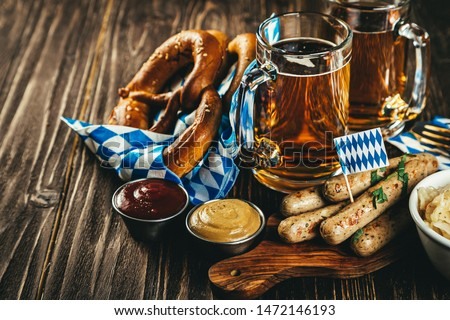 October fest concept - traditional food and beer served at event, wood background #1472146193