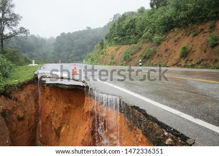 landslide caused by torrential rains occurs broken road asphalt. Broken cement on street. Cracked road from landslid destroyed by heavy rain #1472336351
