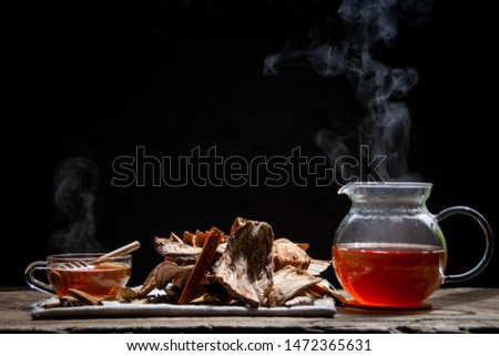 Herbal water in a steamer with minion cups and herbs, roots with a black background - herbal water concept for health