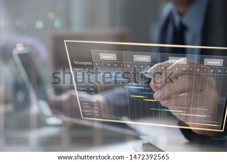 Project management. Project manager updating tasks, milestone progress planning with augmented reality Gantt chart scheduling on virtual screen. Businessman working on digital tablet, laptop computer Royalty-Free Stock Photo #1472392565