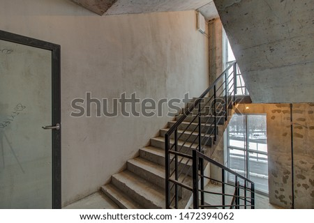 unfinished staircase to basement. Stairs architecture unfinished at basement. Cement concrete staircase on construction site. Empty and Bare Building Interior with Materials and Structure Exposed #1472394062