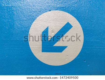 Arrow on a blue textured wall pointing down and to the left. #1472409500