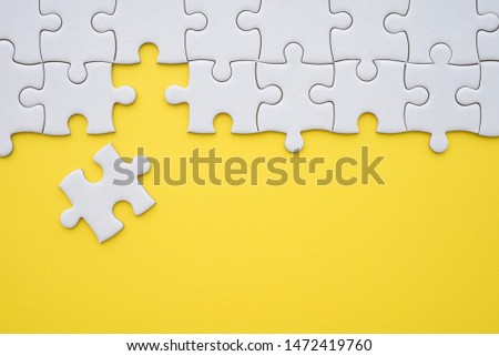 Unfinished white jigsaw puzzle on yellow background with copy space. Business strategy teamwork or problem solving concept. Teamwork is collaborative effort of team to achieve goal or to complete task