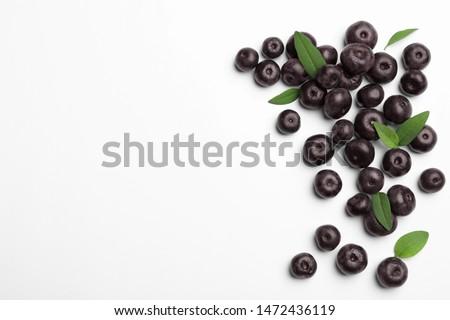 Fresh acai berries on white background, top view Royalty-Free Stock Photo #1472436119
