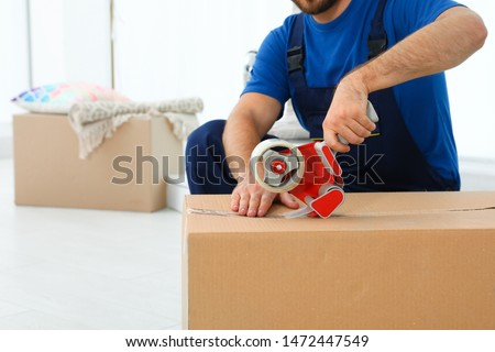 Young worker packing box in room, closeup. Moving service