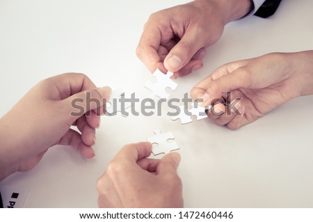 Hand holding the puzzles for the businessmen to work together as a team. Concept of planning work as a teamwork. Closeup of businesspeople holding jigsaw puzzle. #1472460446