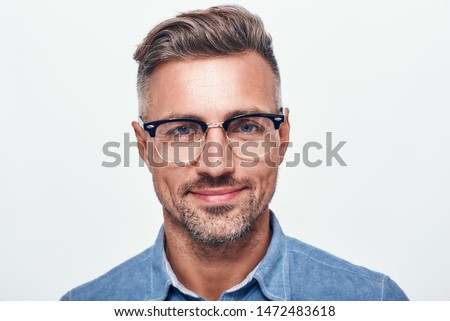 Happy and handsome. Close up portrait of charming bearded man in eyewear looking at camera and smiling while standing against grey background Royalty-Free Stock Photo #1472483618