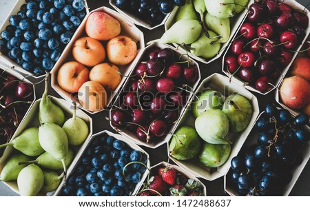 Summer fruit and berry variety. Flat-lay of ripe strawberries, cherries, grapes, blueberries, pears, apricots, figs in wooden eco-friendly boxes over grey background, top view. Local farmers produce #1472488637