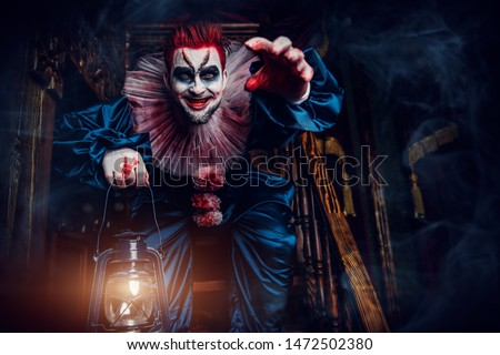 A portrait of an angry crazy clown from a horror film with a lantern on the stairs. Halloween, carnival. #1472502380