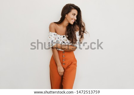 Picture of lady in orange trousers with high waist and white top with floral print. Brunette girl is cute smiling on white background