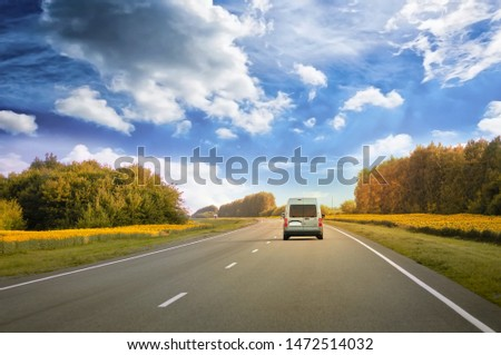 The car rides on an asphalt road, around the yellow fields with sunflowers #1472514032