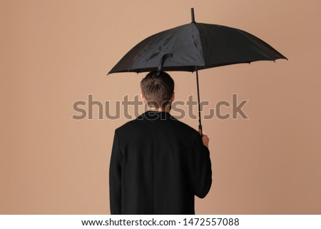 Handsome man with umbrella on color background, back view #1472557088