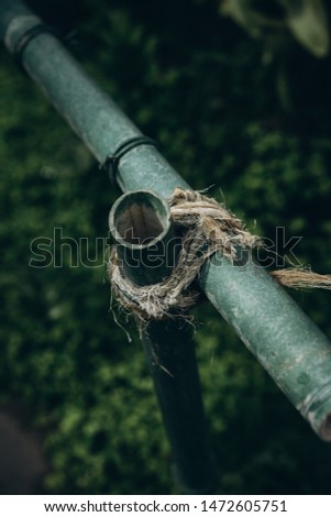 iron pipe wrapped in rope to another pipe, fence, selective focus, film and grain #1472605751