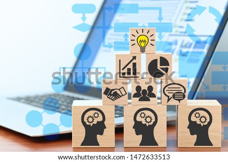Knowledge management and business intelligence concept. Sharing knowledge by technology. Building wood blocks on table. Laptop and flowcharts.