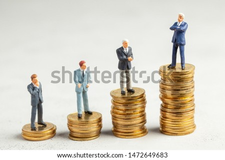 Successful businessman with big profits at the top of the stairs by coins and less successful businessmen with small companies. Adequate investment in the company #1472649683