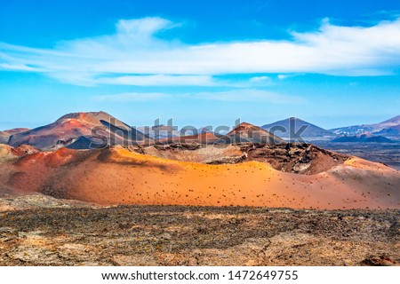 Amazing panoramic landscape of volcano craters in Timanfaya national park. Popular touristic attraction in Lanzarote island, Canary islans, Spain. Artistic picture. Beauty world. Travel concept.
